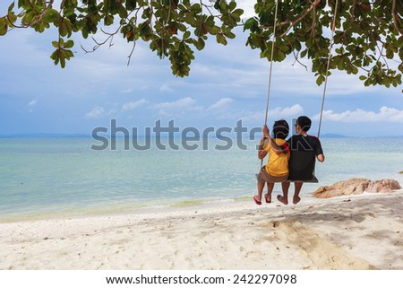 couple in love on a swing on the beach - stock photo