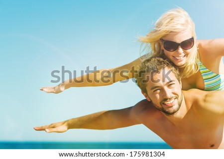 Couple in love on beach in vacation - man carrying his wife on the back close to ocean, they are feeling visibly free and happy