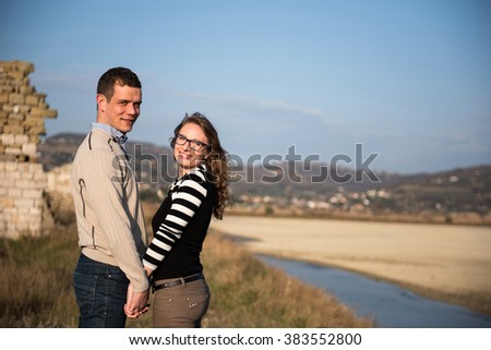 Couple in love on engagement day in natural park, holding hands smiling.