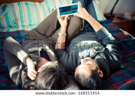 couple in love on the bed using tablet at home - stock photo