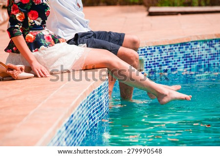 Couple in love playing at the pool, elegant dressed. - stock photo