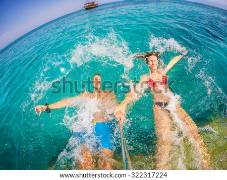Couple in love refreshing on vacation. Jumping at sea. Wide angle selfie shot.