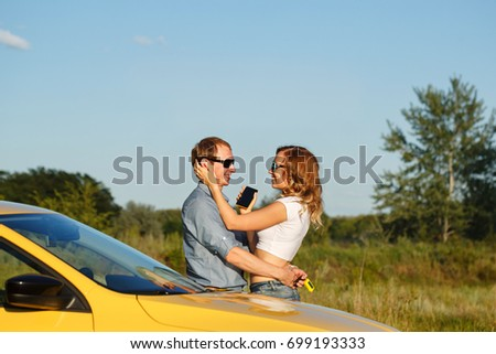 Couple in love. Road Trip. The guy hugs his girlfriend. The girl is holding a cell phone. They are standing by the car