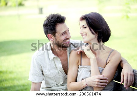 Couple in love seated on a bench together - stock photo