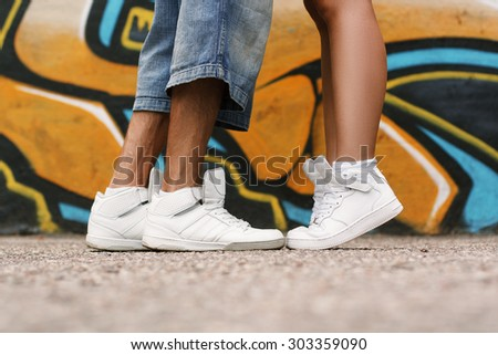 Couple in love. Shoes close up. White shoes on the asphalt. - stock photo