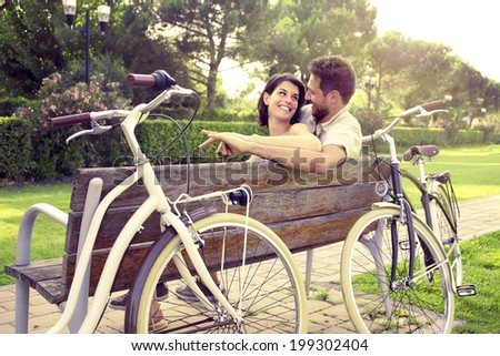 Couple in love sitted togheter on a bench with bikes beside - stock photo