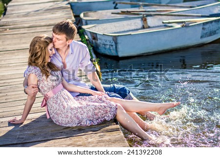 couple in love  sitting on a wooden pier near the boat. Man and woman kiss on the dock, down feet in the water. - stock photo