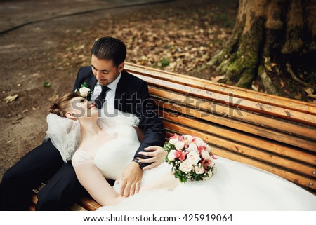 Couple in love sitting  on the bench - stock photo
