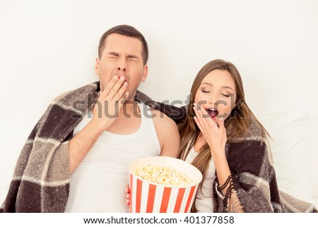 Couple in love sitting with popcorn and yawning while watching film - stock photo