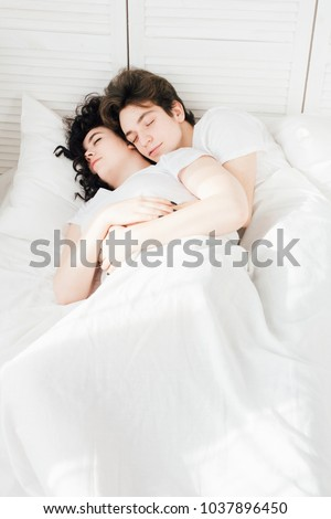 Couple in love sleeps cuddling in bed in the morning. The concept of love and romance. Toning.