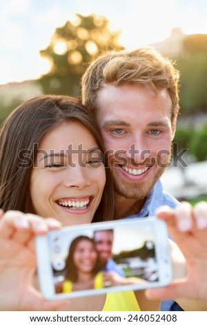 Couple in love taking selfie photo with smartphone. Romantic mixed race couple taking selfies pictures with smart phone camera having fun together outdoors in park. Asian girl, Caucasian guy. - stock photo