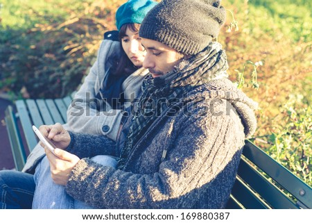 couple in love using tablet at the park in autumn