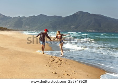 couple in love walk on the sea playing happily at sunset