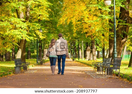 Couple in love walking together in park on a fall day