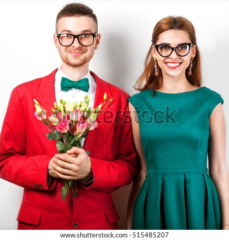 couple in love with a bouquet of flowers in the studio at Christmas, the concept of Valentine's Day