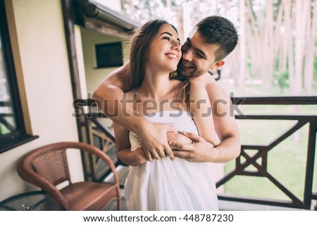 couple in love wrapped in a towel, hugging on the balcony - stock photo