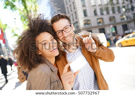 Couple in Manhattan showing shopping card