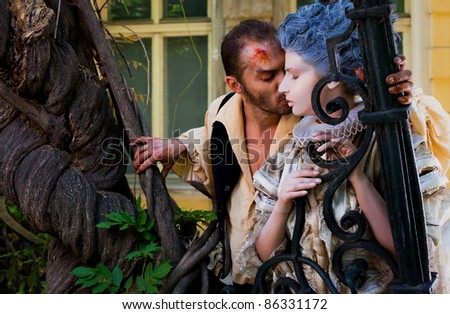 Couple in medieval costumes - male vampire embracing woman with blue wig
