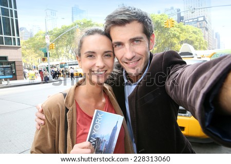 Couple in New York city taking picture with smartphone - stock photo