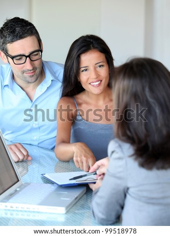 Couple in office signing contractual documents