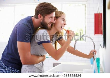 Couple In Pajamas Brushing Teeth In Bathroom - stock photo