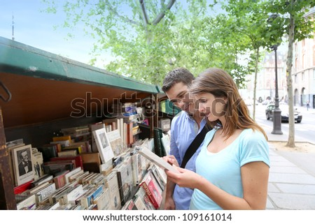 Couple in Paris looking at booksellers - stock photo