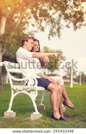 Couple in park sitting on bench, man pointing in front of them - stock photo