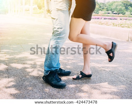 Couple in relationship kissing together while a girl lifting her leg up - stock photo