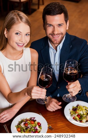 Couple in restaurant. Top view of beautiful young loving couple toasting with red wine while sitting at the restaurant together - stock photo