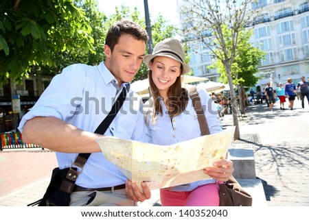 Couple in Santa Ana square of Madrid reading city map - stock photo