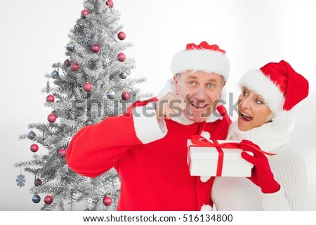 Couple in santa hat holding a gift box near christmas tree against white background