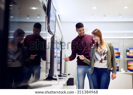 Couple in shopping. They are looking for new tv. They are pointing fingers at tv. Shallow depth of field. - stock photo