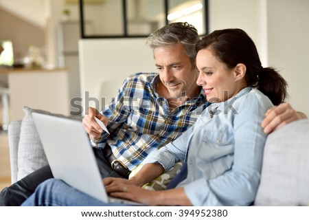 Couple in sofa websurfing and shopping on internet - stock photo