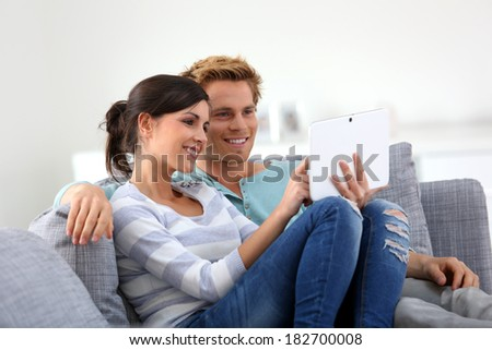 Couple in sofa websurfing on internet with tablet - stock photo
