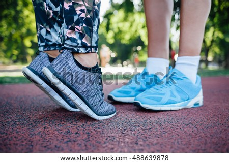Couple in sportswear kissing. Legs of a couple going for a run together.