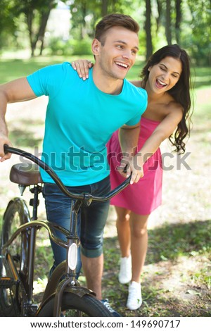 Couple in spring park. Cheerful young couple with bicycle having fun in park