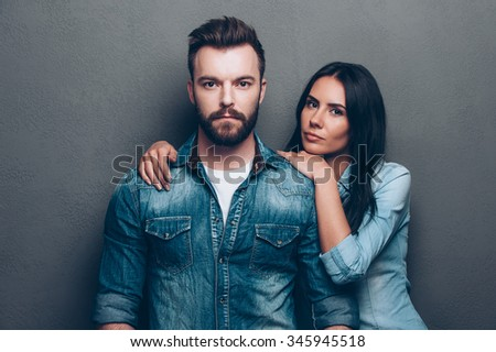 Couple in style. Beautiful young woman bonding to handsome beard man in jeans wear while both standing against grey background