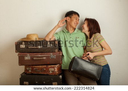 couple in suitcases going on vacation in the studio - stock photo