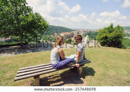 couple in sunglasses sitting on bench - stock photo