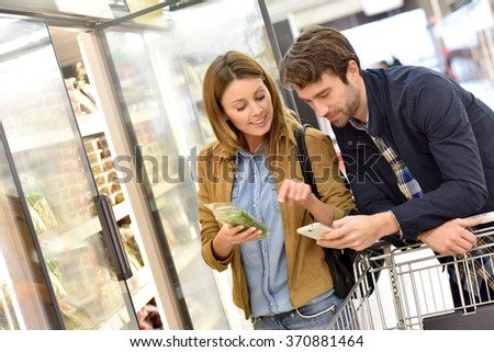 Couple in supermarket reading shopping list on smartphone - stock photo