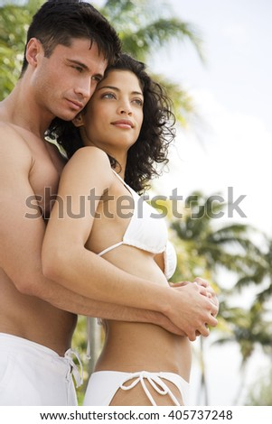 Couple in swimwear on tropical holiday, drinking champagne - stock photo