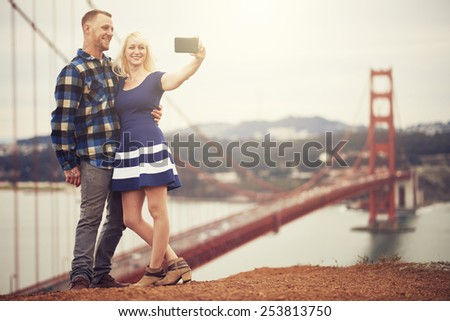 couple in taking selfie in front of golden gate bridge - stock photo