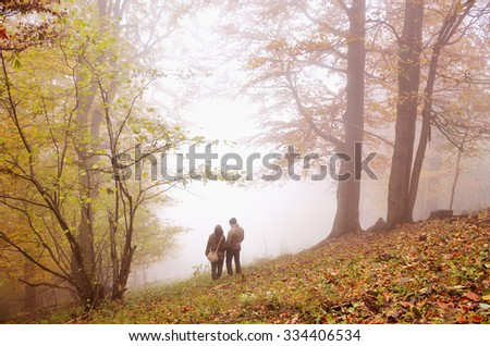 Couple in the autumn misty forest looking to the sky and they are in love  - stock photo