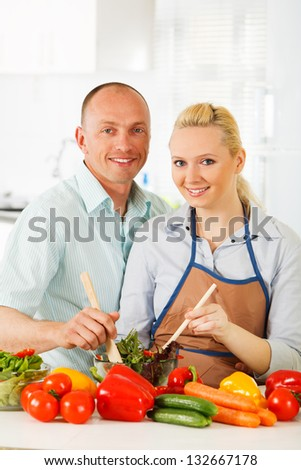 Couple in the kitchen with vegetables. - stock photo
