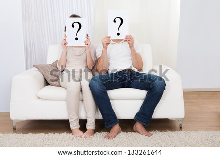 Couple in the living room with question marks in front of their faces - stock photo