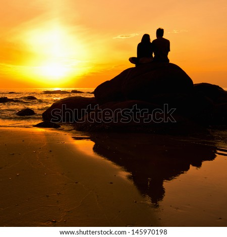Couple in the sea photo silhouette. Sunrise in the morning. - stock photo