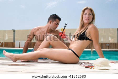 couple in the swimming pool in a hotel - stock photo