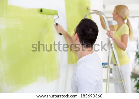 Couple in their new home painting wall in green  - stock photo