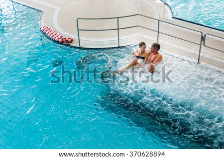 Couple in thermal wellness spa on water massage enjoying the treatment - stock photo