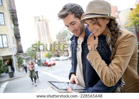 Couple in town connected on digital tablet - stock photo